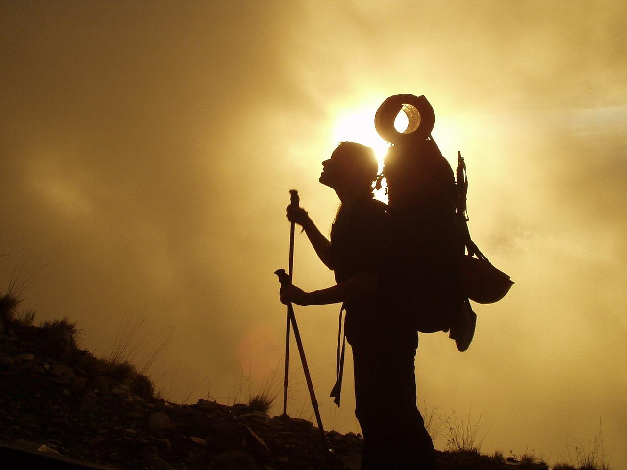 w co się zapakować - walizka, plecak czy torba, człowiek w górach z plecakiem na plecach i kijkami do nordic walkingu w rękach