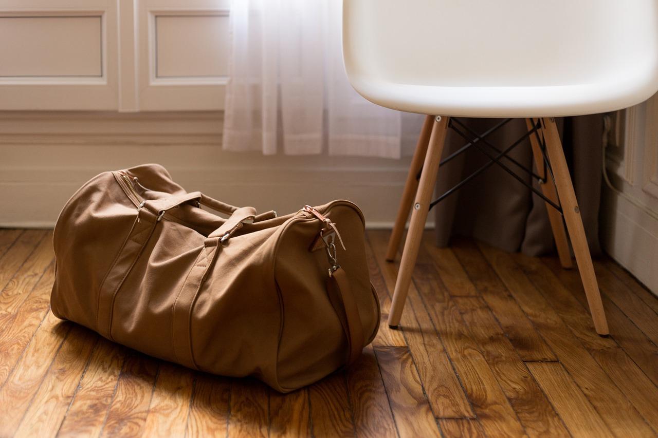 w co się zapakować - walizka, plecak czy torba, torba położona na podłodze, obok stoi krzesło