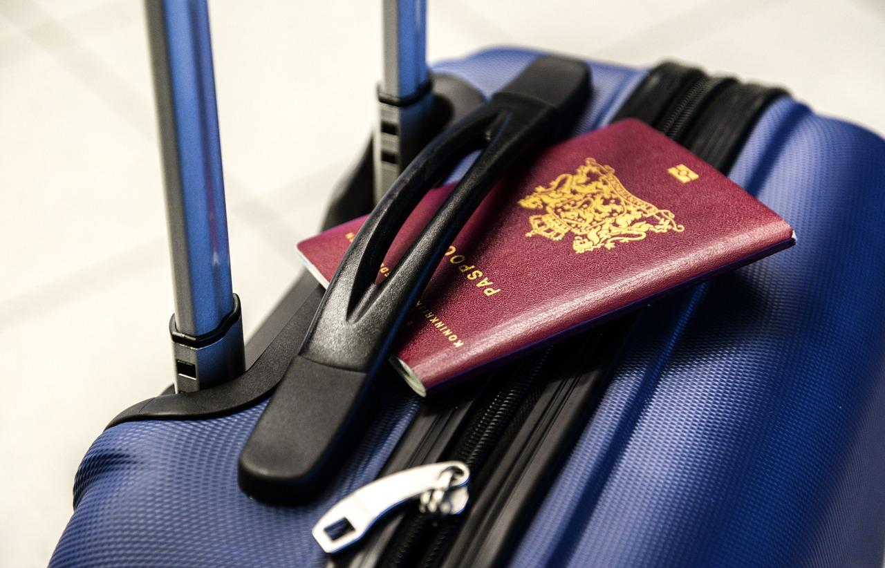 w co się zapakować, walizka na lotnisku, w rączkę wtyknięty paszport